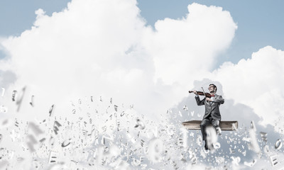 Handsome violinist play his melody and symbols fly around in air