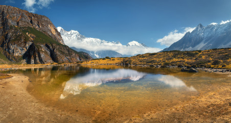Wall Mural - Beautiful view with high rocks with snow covered peaks, mountain lake, reflection in water, blue sky with clouds in sunrise. Nepal. Amazing panoramic landscape with Himalayan mountains. Himalayas
