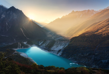 Wall Mural - Mountain valley and lake with turquoise water at sunrise in Nepal. Majestical landscape with high mountains, lake, lightened hills, rocks, sun with yellow light and sky. Bright sunny morning. Travel