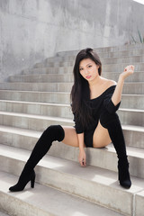 Beautiful exotic woman sitting on steps wearing high  heel boots