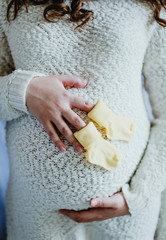Little socks the unborn child in the hands of a pregnant woman