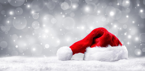 Santa Hat On Snow And Silver Shiny Background