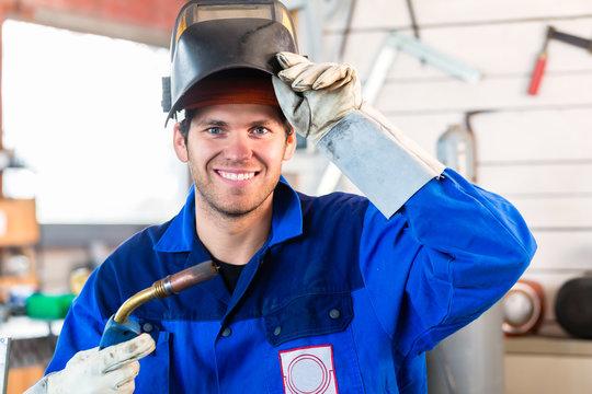 Welder with welding device in metal workshop looking into camera