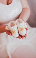 A pregnant woman holds the little booties for your unborn baby
