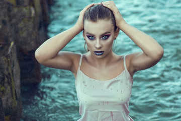 Portrait of young beautiful woman with provocative make up standing in the sea water under the rain and touching her wet hair. Outdoor shot