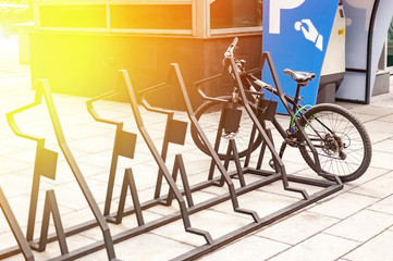 City bike rental system. Bicycle parts are large. Parking bicycles on city streets. With tinting and blurring.