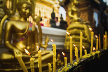 Candle light in front of buddha image.