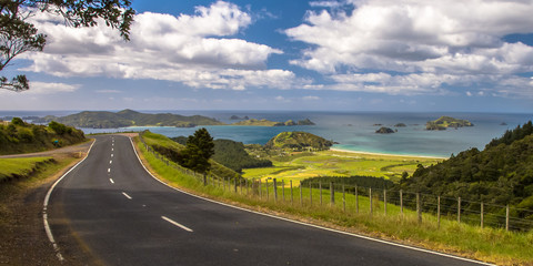 Inviting road through New Zealand countryside with blue sea