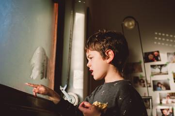 boy writing on a foggy window