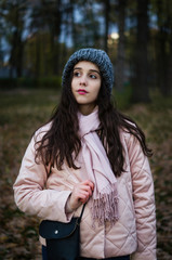 Young pretty girl walking autumn cold evening park
