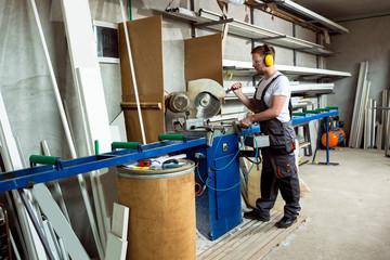 Worker cutting PVC profile with circular saw