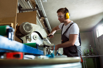 Worker in the workshop cuts pvc profile