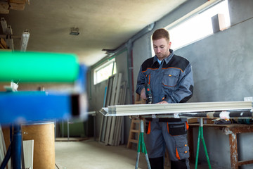 Worker with drilling mashine in workshop