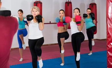 group of serious women and their trainer are boxing in gym