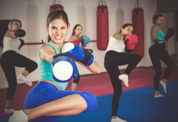 Portrait of sporty girl who is boxing with group in gym
