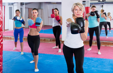 Portrait of concentrated mature female who is training box exercises with group in gym