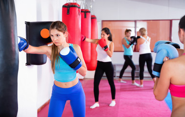 Sporty girl is boxing near punching bag in gym.