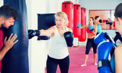mature female is doing exercises with punching bag in gym