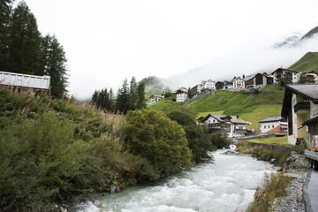 Stream and Glacier from Alps highest and most extensive mountain range flowing passed at Villages of Tschlin and Ramosch in Switzerland