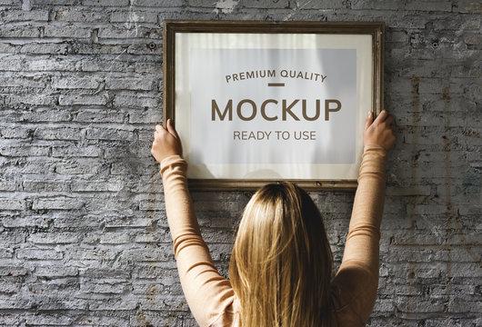 Woman hanging a photo frame mockup