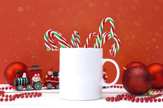 White coffee mug  with Christmas decorations on red background.