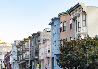 Row of historic pastel colored buildings with classic bay windows on Filbert Street in San Francisco, California
