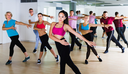 friendly men women posing in fitness studio