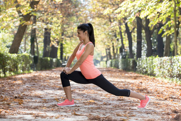 beautiful hispanic sport woman in sportswear stretching body next smiling happy doing flexibility exercises