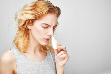 The treatment of rhinitis. Girl dripping nose drops