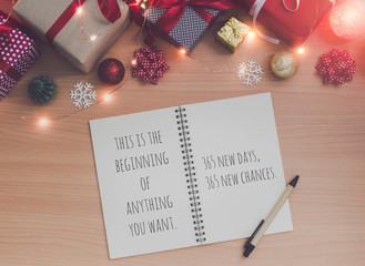 Motivation and inspiration quote on Note book and pen with Christmas and New Year holidays gift box with decorative ornament on wooden table.Gifts and congratulations concept.