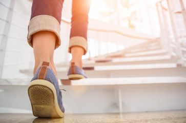 Young adult woman walking up the stairs with sun sport background. Fotomurales