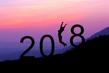 Silhouette young woman jumping over 2018 years on the hill at sunset.