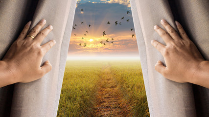 man and hope concept . man opening window curtains and seeing the city above the sunrise sky Wall mural