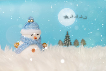 Happy snowman standing in blue winter christmas snow background. Merry christmas and happy new year greeting card with copy-space. Christmas celebration holiday background