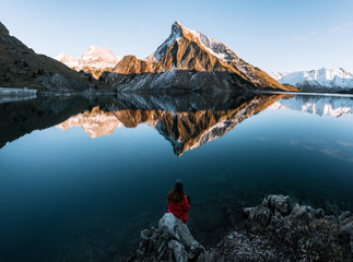 Young adult woman wearing red jacket enjoying the view over a mirror-like mountain lake in the Austrian Alps during sunset