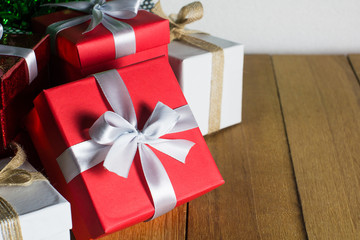 Close up red and white gift box on wood table background with copy space. Christmas, New year, Valentine or Birthday concept. Still life.