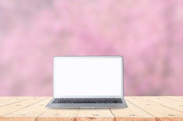 Laptop with blank white screen on table. pink nature background, blurred background