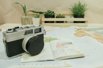 camera, passport, world map placed on wooden table has plants in vase are background. this image for business, travel, photography, equipment, map concept