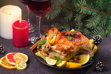 Chicken or turkey with lemons, oranges, limes and spices on Christmas and New Year background. Two glasses of wine, horizontal