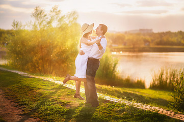 Beautiful bright fairy walk of a loving couple in the summer at sunset. A guy in a white shirt and jeans with a girl in a sarafan and a straw hat hugs and dances against the background of a pond in th