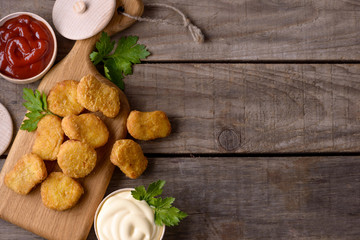 Chicken nuggets and sauces on wooden background