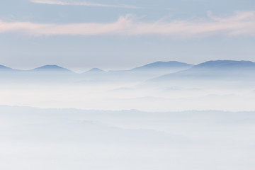 Fog filling a valley, with layers of mountains and hills and various shades of blue