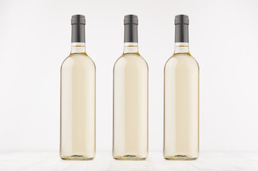 Three transparent wine bottles with white wine on white wooden board, mock up. Template for advertising, design, branding identity.