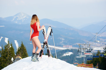Back view of pretty girl skier wearing red bodice, enjoying beautiful view of ski resort, standing with skis on the top of the slope. Mountains, forests, ski slopes and ski-lift on the background