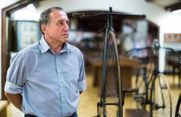 mature man examines the exhibit in museum