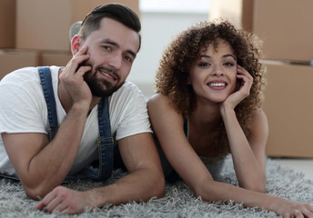 Portrait of a married couple lying on the floor after moving