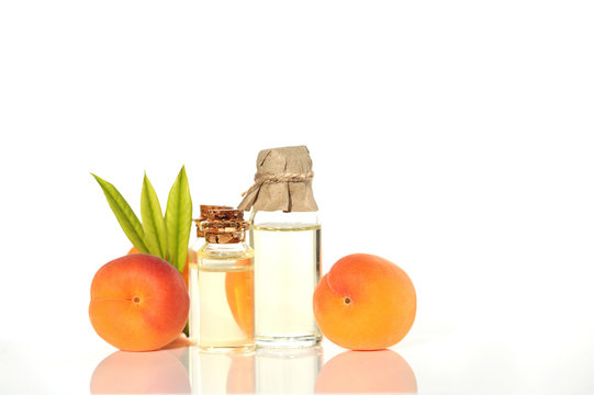 Apricot Oil. apricot oil in a glass bottle and  ripe apricots on a white background. Vegan Botanical Cosmetics