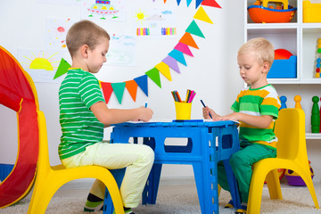 Two brothers draw pictures in the kids room.