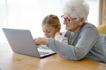 Little girl with grandmother using laptop computer