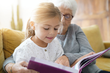 Little girl reading book with grandmother